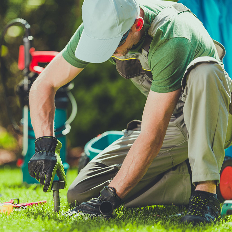 Technician Repairing a Lawn Sprinkler