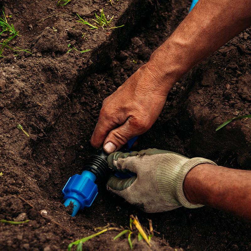 man repairing sprinkler system